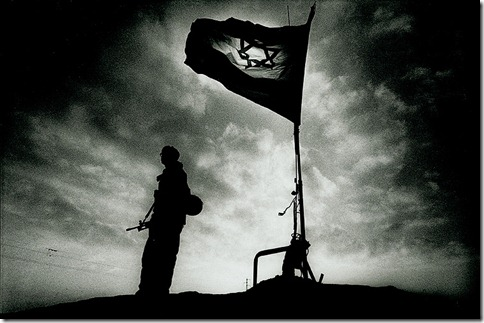 Israeli soldier stands beneath a flag